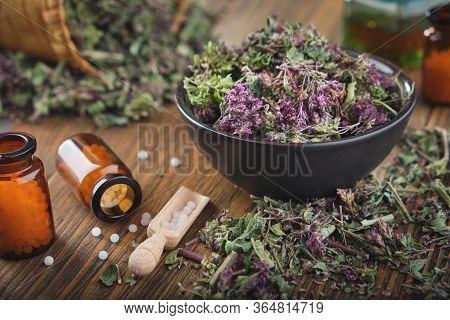 Bottles Of Homeopathic Globules. Origanum Vulgare Or Wild Marjoram Flowers In Bowl. Bottle Of Essent