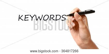 Woman Writing Word Keywords On Transparent Board Against White Background, Closeup