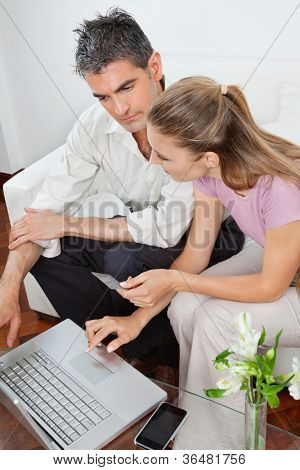 High angle view of couple with laptop using credit card for online shopping