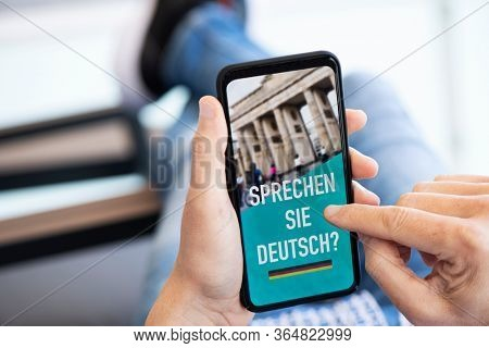 closeup of a young caucasian man, wearing casual clothes, sitting in a chair indoors, having his smartphone in his hand with the text do you speak German written in German in its screen