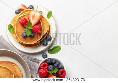 Delicious homemade pancakes with summer berries for breakfast. Top view with copy space