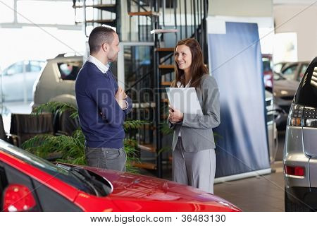Man speaking to a woman in a dealership