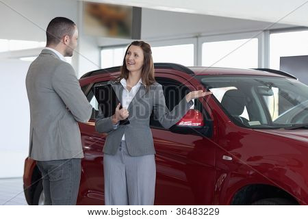 Businesswoman showing a car to a client in a dealership