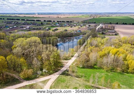 Aerial View Of A Small Rural Village Among Green Fields In Sunny Day. Spring Landscape Of Countrysid