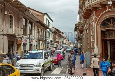 CUENCA, ECUADOR - MAY 07, 2019: Busy urban street with people passing by in the center of Cuenca, colonial town in Ecuador