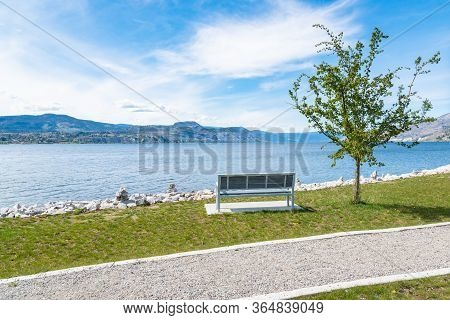 Park Bench On The Lakeshore In The Village Of Naramata, With View Of Okanagan Lake And Blue Sky