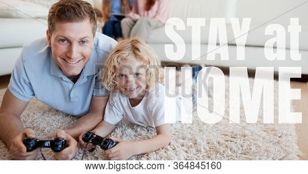The words Stay at Home with a Caucasian man and girl lying on floor, playing video game. Public health pandemic coronavirus Covid 19 social distancing and self isolation in quarantine lockdown concept