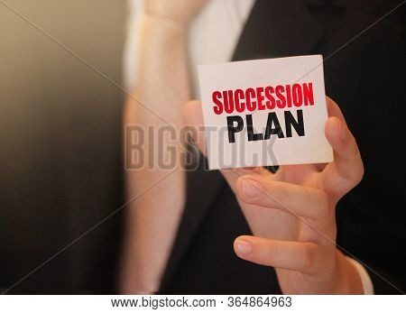 Succession Plan Words On A Card In Hand Of Businessman. Business Profit And Success Concept