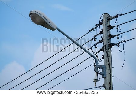 Close Up Street Lamp Hanging On Electric Pole Isolated On Blue Clouds Sky Background. Electric Pole