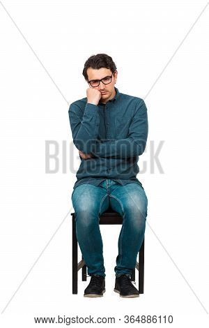 Full Length Of Annoyed Businessman Keeps Hand Under Cheek, Seated On A Chair Isolated On White Backg