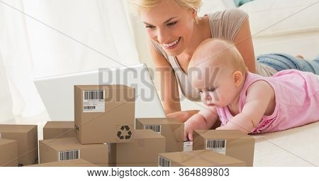 Caucasian woman and baby girl using laptop computer at home shopping on line with pile of cardboard parcel boxes next to them. Online shopping ecommerce social distancing and self isolation in