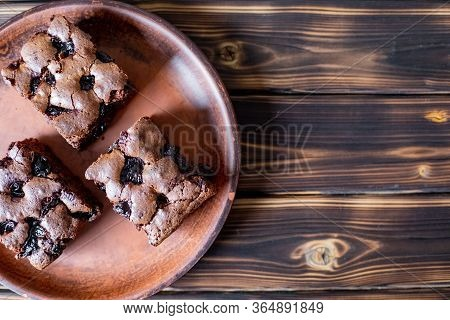 Cherry Brownie Close-up. Tasty Cherry Brownie Lies In A Plate On A Wooden Table. Brownie Sprinkled W
