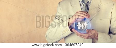 Insurance Concept. Family Insurance. The Insurance Agent Holds A Protective Sphere With A Family Ima