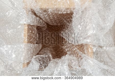 Bubble Wrap On An Open Cardboard Box. Soft Packaging For The Safety Of Shipments