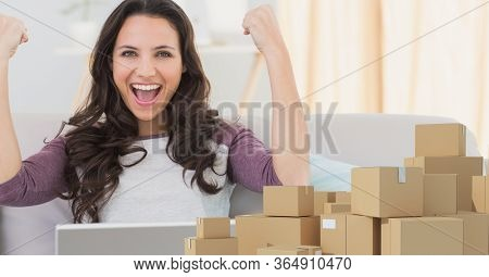 Happy Caucasian woman smiling with her arms in the air, using laptop computer at home shopping on line, pile of cardboard parcel boxes next to her. Online shopping ecommerce social distancing and self