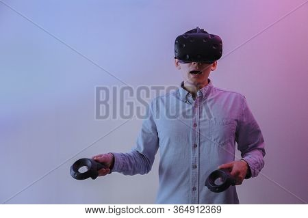 A Man In Virtual Reality Glasses With Gamepads In His Hands Masters Virtual Reality. A Man Is Lit By
