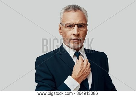 Handsome Senior Man In Full Suit Looking At Camera And Adjusting His Tie While Standing Against Grey