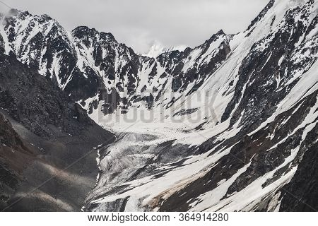 Atmospheric Minimalist Alpine Landscape Of Big Snowy Mountain With Massive Glacier. Cloudy Sky Over