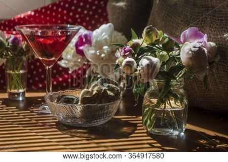 Solemn Rustic Still Life With Glass Of Red Drink With Cakes In A Bowl Surrounded By White Flowers On