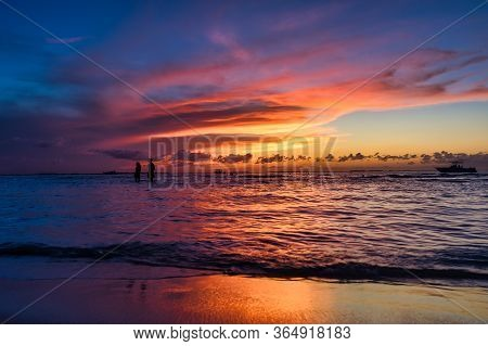 Young Couple Strolls At Low Tide On A Tropical Island Holbox Mexico. Incredible Sunset On The Beach.