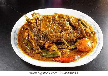 Serving Of Curry Fish Head With Okra And Tomato, Popular Delicacy In Malaysia
