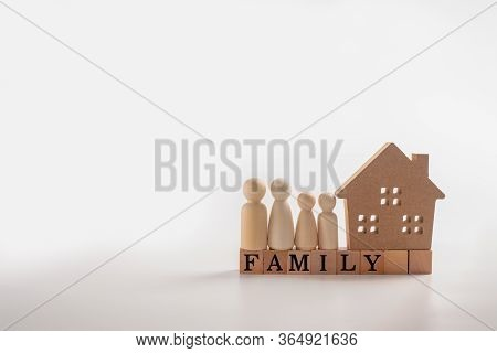 Wooden Figures Family Standing Beside A Wooden House On A Wooden Cube That Writes The Word Family. T
