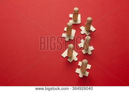 Wooden Figures On Puzzles On Red Background As A Symbol Of Team Building. Organization Group People