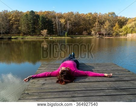 Girl In A Pink Long Sleeve T-shirt And Pants Lying Down On A Wooden Bridge Over The Lake With Open A
