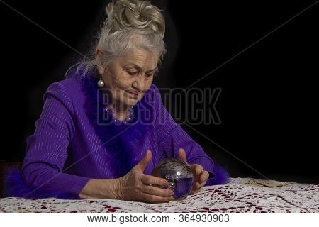 Elderly Female Magician With A Glass Ball. Fortuneteller At Work.