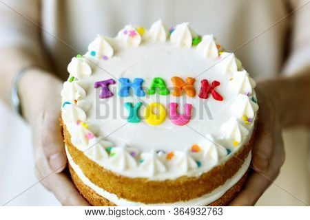 Hands holding cake with colorful rainbow letters spelling thank you