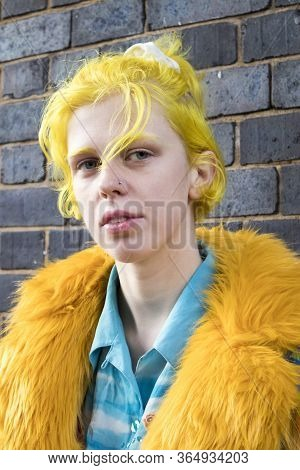 A Girl With Yellow Hair In A Faux Fur Coat, Blue Shirt With Palm Trees And Skinny Jeans Poses Agains