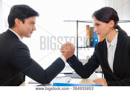 Boss And Employee Arm Wrestling With Face To Face On Desk At Their Office. Coworker And Colleague Or