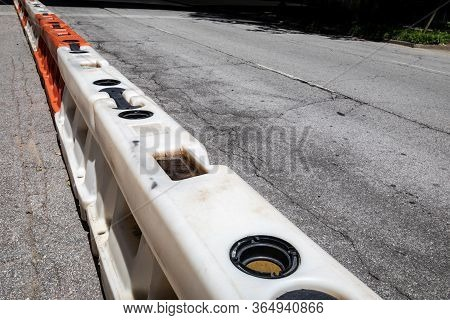 Cracked Asphalt City Street Divided With White And Orange Hard Plastic Traffic Barricades, Urban Dec