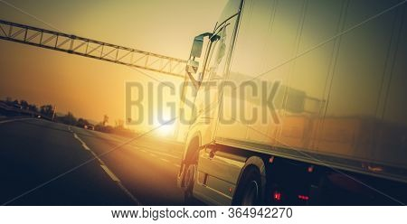 View Of Open Road And Semi Truck On Highway With Yellow Hazy Sunset.