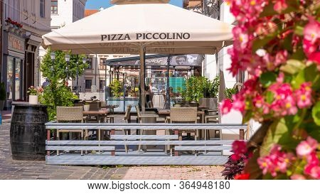 Gyor Hungary 02 16 2020: The Terrace Of A Cozy Pizza Piccolino Restaurant With Few Guests In The Cen