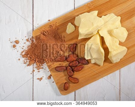 Pieces Of Natural Cocoa Butter, Cocoa Powder And Cocoa Beans On Wooden Cutting Board. Top View. Flat