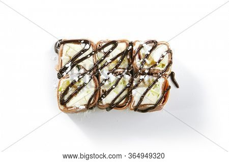 Chocolate pancake with kiwi, coconut flakes on white background top view. Spring roll with mascarpone and cream cheese, chocolate topping and condensed milk closeup. Sweet meal with glaze decoration