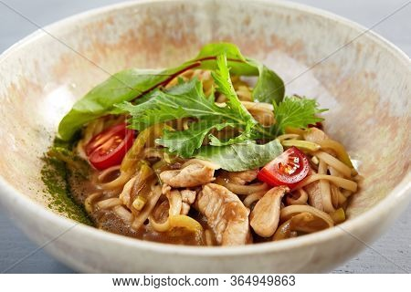 Asian noodles with chicken in beige bowl. Pasta with dietary meat close up. Delicious delicatessen, served restaurant meal, tasty flour product with tomato and greenery decorations