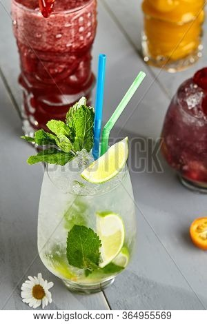 Classic mojito and berry smoothie in glasses with cocktail tubes. Cold desserts with ice cubes, sweet soft drinks with fruits close up. Gourmet appetizer, restaurant meal, sugary beverage