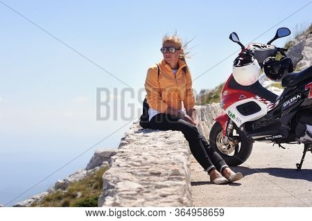 Split, Croatia - July 12, 2019:the Girl On The Gilera Scooter Stopped In The Mountains Of Croatia. A