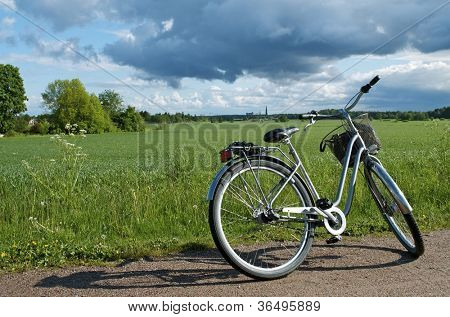 Bicycle parked on the side of a path, with countryside and fields in background: Uppsala, Sweden