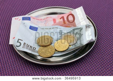 Euro tipsand payment for bill on on restaurant table.