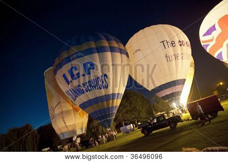 NORTHAMPTON, ENGLAND - AUGUST 18: Hot Air Balloons in night time burn demonstration at the Northampton Balloon Festival, on August 18, 2012 in Northampton, England.