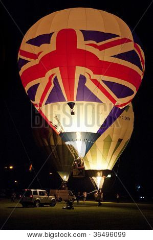 NORTHAMPTON, ENGLAND - AUGUST 18: Hot Air Balloon with union Jack flag launching at night at the Northampton Balloon Festival, on August 18, 2012 in Northampton, England.
