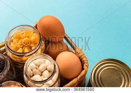 Donation Box With Eggs, Pasta, Kidney Bean And Tea In Glass Jar And Tin Can In The Blue Background I
