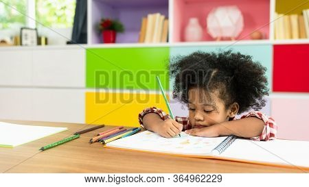Young African American Kid Girl Drawing With Colored Pencil, Preschool Child Study At Home School. C
