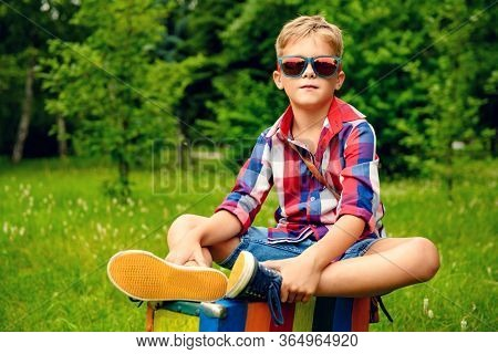 A boy is sitting on a suitcase in the coutryside. Summer fashion concept for kids.