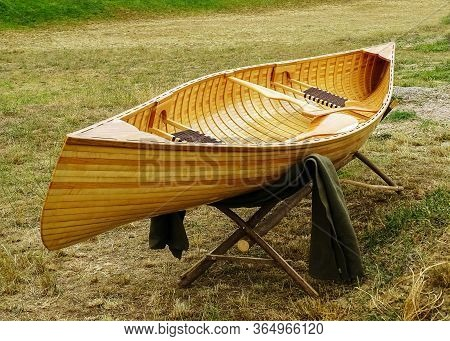 Wooden Boat Placed On A Wooden Stand In The Meadow.after The Boat And Over The Stand There Is A Blan