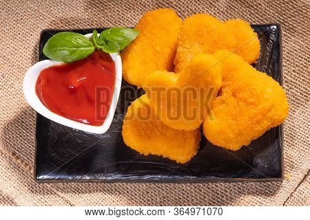 Breaded Chicken Nuggets With Ketchup On A Black Ceramic Kitchen Board On A Wooden Background. Fast F
