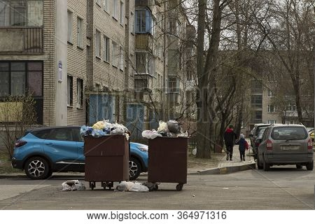 Two Brothers Children Go And Hold Hands. Children Walk Past Containers With Rubbish; They Walk Among